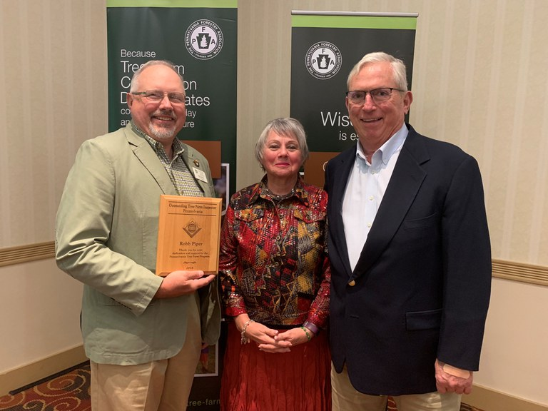 Robb Piper (left) receives the 2018 Outstanding Inspector of the Year Award from John and Maureen Burnham (Photo by Caleb Wright)